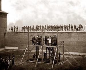 "Four soldiers wait below the gallows to ""spring the trap"""